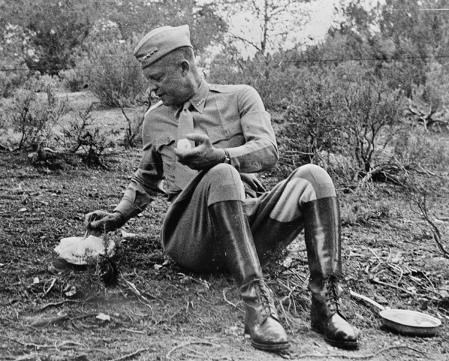 Supreme Commander of Allied Forces in the Mediterranean, General Dwight D. Eisenhower sits on the ground to eat a C Ration during an inspection of Allied troops in Tunisia in 1943. The C Ration fed hungry American soldiers into the 1980s.