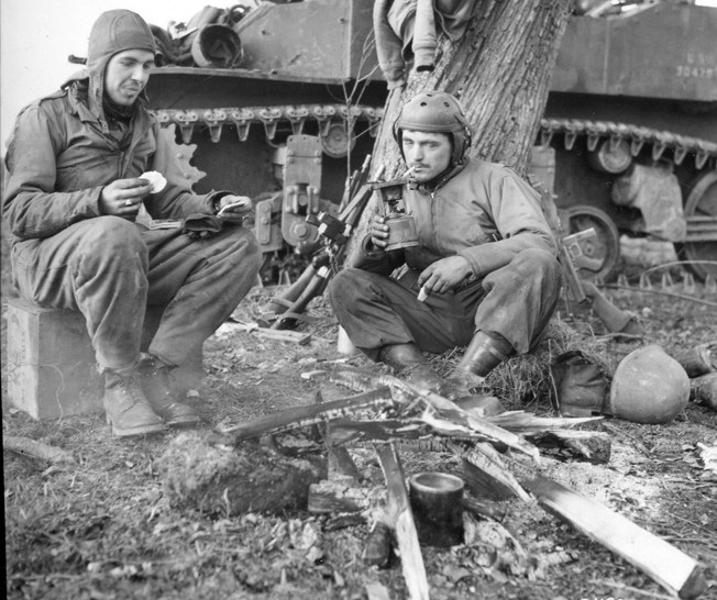 A pair of hungry  American tankers of the VII Corps pause  to eat K Rations during a break in the fighting  in Belgium in  December 1944.