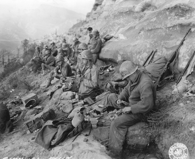 During combat operations in Italy in October 1944, soldiers of the 91st Infantry Division rest against a rocky outcropping and eat K Rations. The K Ration was relatively easy to transport, and it was alternately loved and hated by GIs the world over.