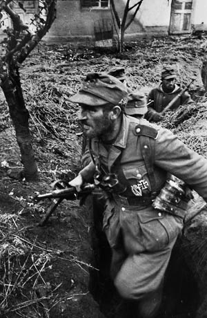 The strain of combat evident on his face, a German infantryman and his comrades move cautiously along a ditch on the Eastern Front. A total of 55 soldiers managed to escape Ternopil and make their way to the main German line.