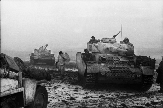 Two German PzKpfw. IV tanks advance along a bleak, muddy landscape in December 1943, as panzergrenadiers trudge down a Ukrainian road that has turned into a quagmire or hitch rides on the tanks. Note the side armor on the vehicles, intended to detonate antitank shells prior to impact with the tank's hull.