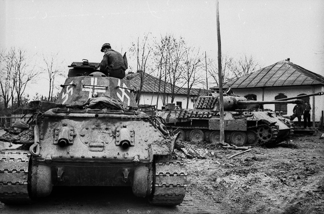 Photographed somewhere in the Ukraine, a captured Soviet T-34 medium tank has been pressed into service with the German Army and painted with swastikas and a white cross for recognition purposes.