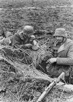 """Tarnopol, Ukraine: 1944. German Soldiers in their Emplacement near Ternopil. German soldiers have a meal in their emplacement in the median sector of the Eastern Front. ©SZ Photo / Scherl / The Image Works NOTE: The copyright notice must include """"The Image Works"""" DO NOT SHORTEN THE NAME OF THE COMPANY"""