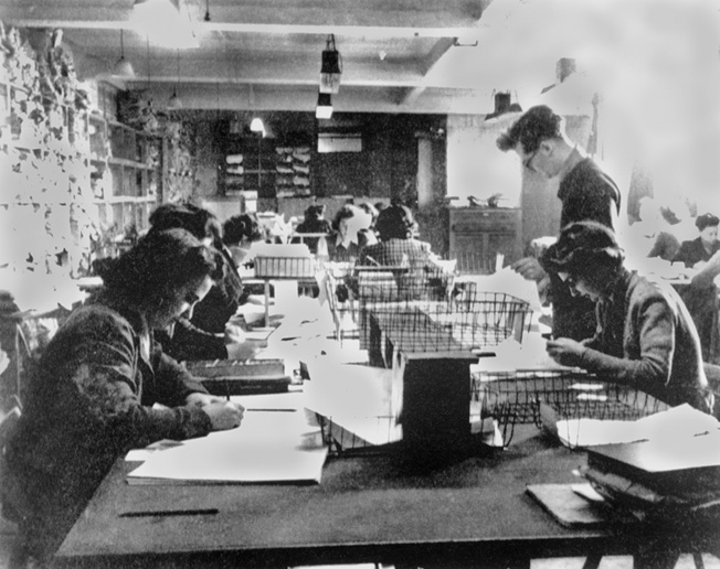 In Hut 3 at Bletchley Park, civilian and military personnel work together to decipher intercepted German communications.