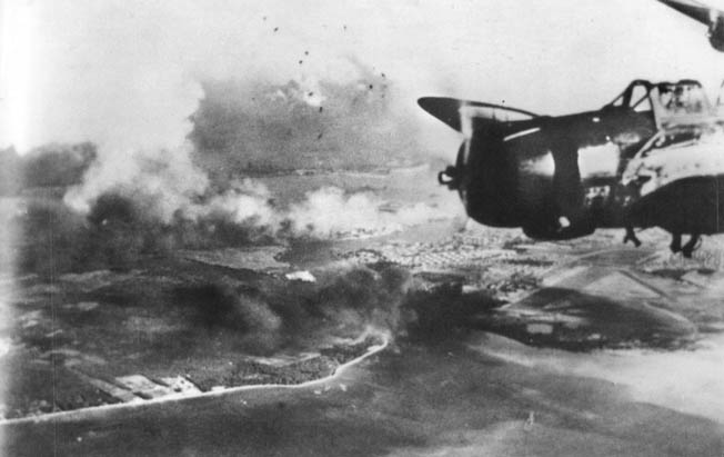 A Nakajima B5N torpedo bomber from the carrier Kaga flies high above smoldering Pearl Harbor. Note the black puffs of antiaircraft bursts.