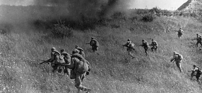 Red Army infantrymen advance as a shell explodes in front of them and throws up a curtain of smoke and debris. Out of the frame, Soviet tanks have taken the lead in this assault somewhere in the Ukraine.