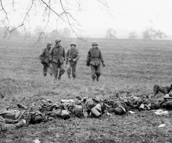 90th Division soldiers encounter a line of German soldiers killed during the battle for Fort Koenigsmacker.