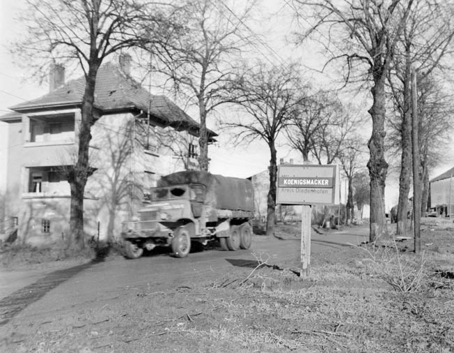 The Germans placed mismarked signs to confuse the advancing Americans. Here, a deuce-and-a-half truck rushes through the village of Koenigsmacker, whose city limit sign has been corrected by Third Army units.