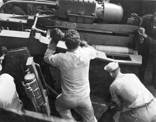 Crewmen aboard the destroyer USS Nicholas load ammunition for the main 5-inch guns of the warship before the battle. The Nicholas utilized radar to search for enemy vessels during the Battle of Kula Gulf.