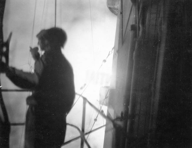 Photographed aboard the light cruiser Honolulu during the heat of the Battle of Kula Gulf, U.S. Navy personnel coolly discharge their duties.