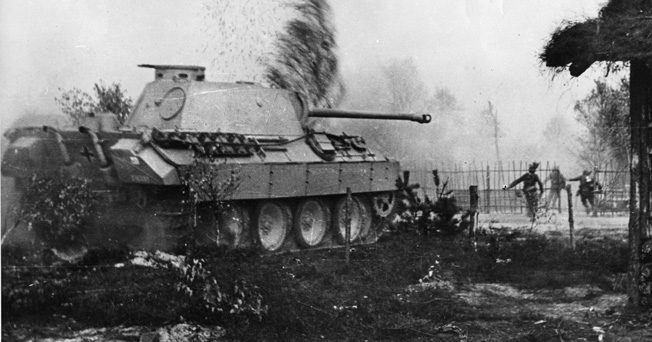 """Men of the Grossdeutschland Division, accompanied by a PzKpfw V """"Panther"""" tank, enter a village in southern Russia, 1944."""