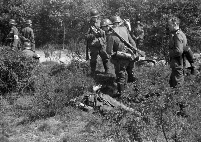 Three German soldiers view a curiosity: a dead Dutch defender, May 11, 1940. In five years, scenes of death and destruction would be commonplace.