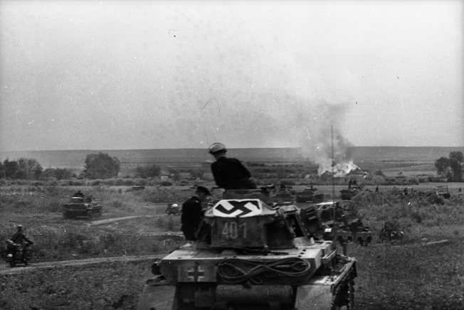 With a Nazi Party flag draped across its turret to show accompanying Luftwaffe planes that these are German troops, columns of tanks roll toward a burning Soviet village.
