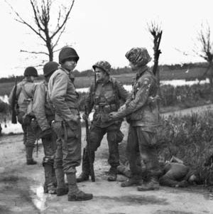 Paratroopers of the 82nd Airborne Division with helmet covers fashioned out of parachute silk chat with 4th Infantry Division soldiers near La Fière while a German soldier lies dead at their feet. Some of the flooded fields are visible in the background.