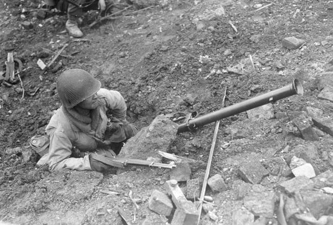 During the fighting at La Fière, American paratroopers of the 82nd Airborne Division handled bazookas with great skill and held German armor at bay. This paratrooper takes cover beside a roadway near La Fière, his bazooka nearby.