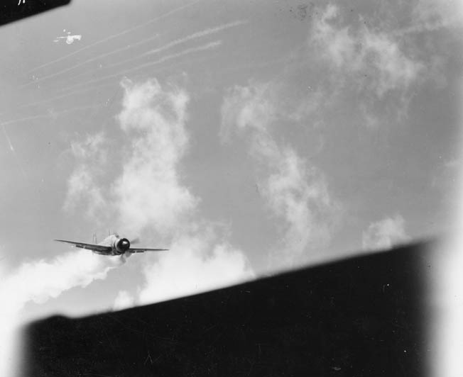 """Billowing smoke after being struck by AA fire, this Yokosuka D4Y3 Suisei """"Judy"""" is about to smash into an American ship."""