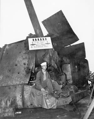 After the Laffey returned to Seattle for repairs, the ship was opened to the public. Here, a sailor sits on a damaged 5-inch gun turret that was hit by two kamikazes which, as the sign says, killed six sailors. Today the Laffey is a museum ship docked at Charleston, South Carolina.