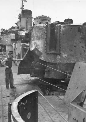 A Seattle shipyard worker examines damage to the Laffey's aft 5-inch gun turret. Note bullet and shrapnel holes in the armor plating.