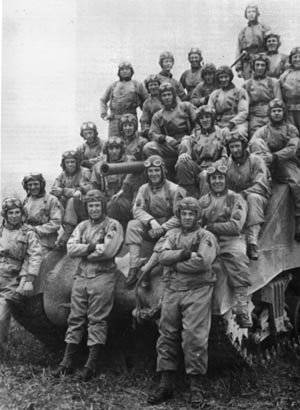 Pictured during training in England prior to their deployment to the European continent, members of Captain Jimmie Leach's B Company, 37th Tank Battalion gather atop one of their M4 Sherman medium tanks for a group photo.