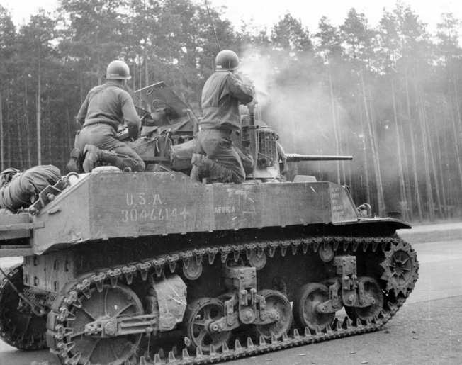 "A 3rd Armored Division crewman with a .30-caliber machine gun mounted on an M3 ""Stuart"" light tank fires on enemy troops in the woods flanking a highway near Leipzig, April 17, 1945. Although the war was nearly over, some Germans stubbornly resisted, preferring death to dishonor."