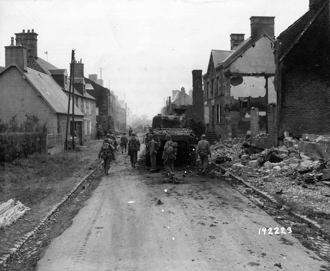 "An M4 ""Sherman"" medium tank from the 3rd Armored Division rolls cautiously through a shattered German village."