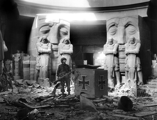 Seemingly being watched by displeased Germanic statues, a 69th Infantry Division soldier stands amid the rubble inside the Völkerschlachtdenkmal shortly after Leipzig was taken.