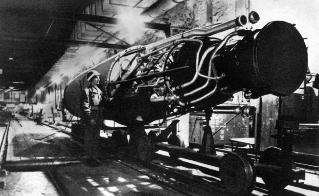 An American soldier inspects the engine of a V-2 pilotless rocket bomb on the assembly line at the underground factory near Nordhausen. The V-1 rockets were also assembled here by slave laborers from concentration camps.