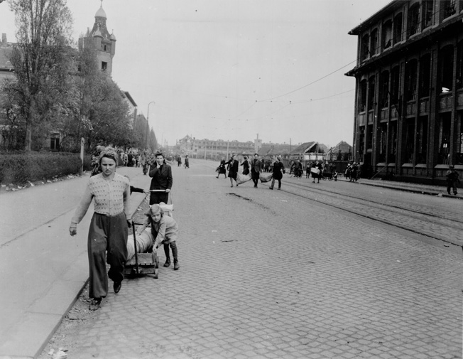 Their faces full of concern for the unknown future, Leipzig residents emerge from hiding as German resistance ends and American occupation begins.