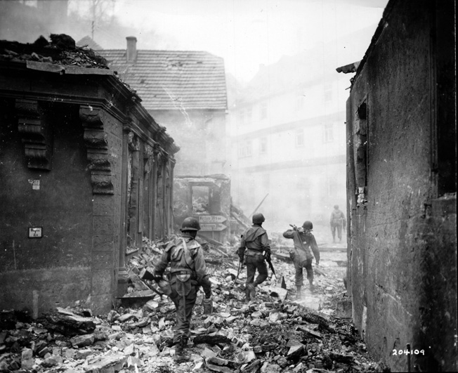 GIs from a machine-gun squad move through the rubble of a destroyed German town in early April 1945.