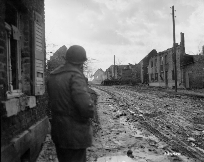 As the front lines moved closer to Berlin, the fighting became more intense. Here a soldier from the 104th Infantry Division looks for any signs of life in a disabled German tank in the middle of a ruined village.