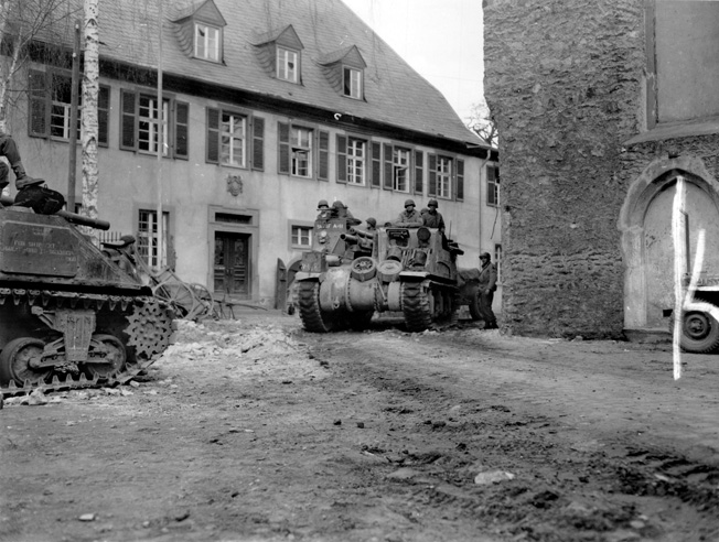 "An M7 105mm howitzer motor carriage (""Priest"") of the 9th Armored Division advances through the streets of a German town, April 1945."