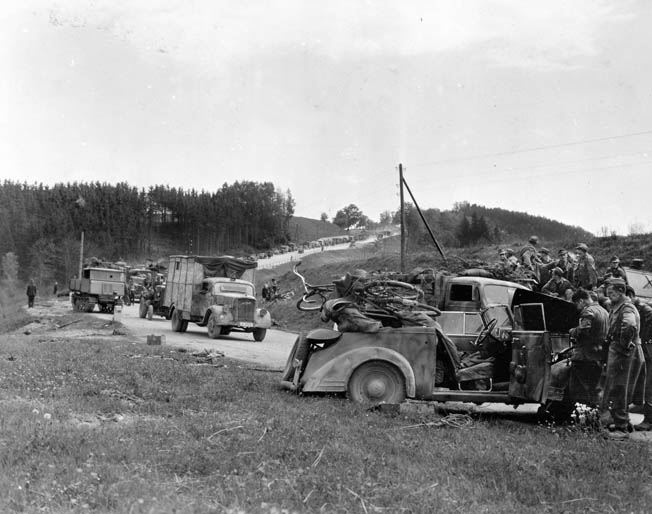 "A convoy of surrendering SS troops near Enns, Austria. The 65th Division soldiers showed little compassion for the SS, infamous for committing atrocities. Tulper recalled that the division ordered, ""Take no prisoners."""