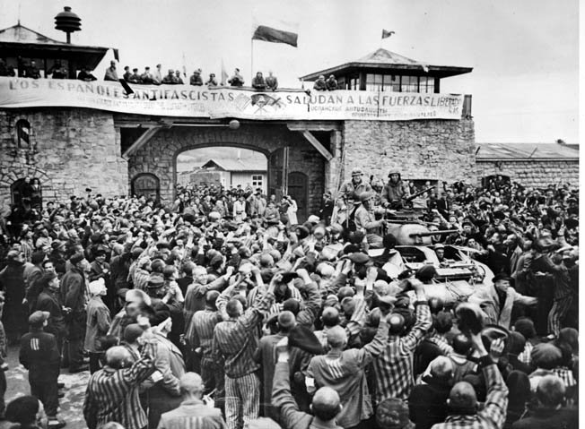 "Mauthausen survivors cheer the soldiers of the 11th Armored Division of the U.S. Third Army one day after their actual liberation. The banner, written by Spanish inmates, reads, ""The Spanish Anti-Fascists Salute the Liberating Forces."""
