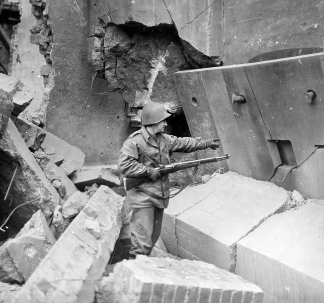 A 65th Division soldier inspects the ruins of a shattered German bunker near Saarlautern, Germany, southeast of Luxembourg on the Saar River, where Tulper briefly set up his radio.