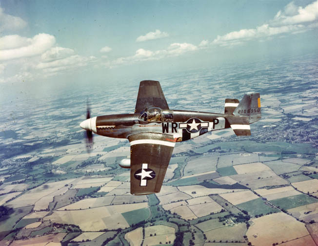 A North American P-51B Mustang fighter in flight somewhere above the English countryside. The P-51 was conceived as a dive bomber, but the installation of the British Rolls Royce Merlin engine, replacing the original Allison powerplant, transformed the Mustang into perhaps the finest American fighter plane of World War II.
