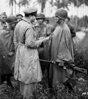 General Douglas MacArthur congratulates poncho-clad Lieutenant Marvin J. Henshaw after awarding him the DSC for being the first man ashore on Los Negros on February 29. Unfortunately, Henshaw would die by drowning on April 6, 1944.