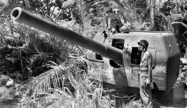 Soldiers from the 99th Field Artillery Battalion inspect a Japanese naval gun emplacement guarding Momote airfield.
