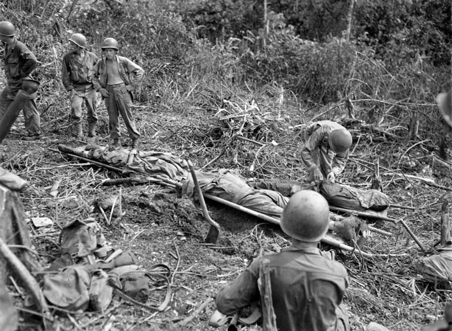 Three KIAs from the 5th Cavalry Regiment lie on stretchers before being buried in a temporary cemetery on Los Negros. The 1st Cavalry Division lost 290 soldiers killed and nearly 1,000 wounded.