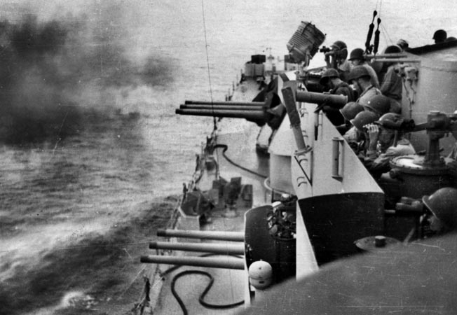 ix-inch guns of the cruiser USS Phoenix bombard Los Negros on the morning of February 29 as the cavalrymen prepare to land on the island.