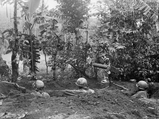 Three soldiers manning a machine-gun post are on the alert for an enemy counterattack on their position, November 1944.