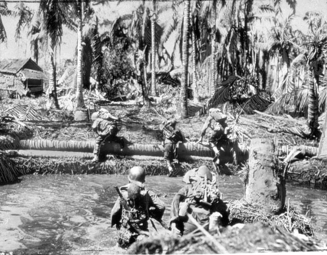American troops cross a stream while pursuing the enemy through a Leyte jungle.