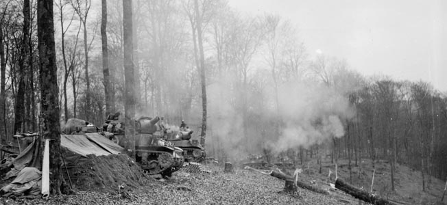 Self-propelled 105mm howitzers of Troop E, 106th Cavalry fire on German positions in France on December 20, 1944. To the north the Battle of the Bulge was raging, and this image was captured only three days before the 106th Cavalry Squadron was ordered to relieve elements of the Third Army, which hurried northward to the relief of the encircled city of Bastogne, Belgium.