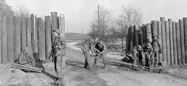 On January 2, 1945, the day after the German Army launched Operation Nordwind, engineers of the 106th Cavalry Squadron prepare a roadblock to slow the enemy advance a half mile from the town of Ludweiler, Germany.