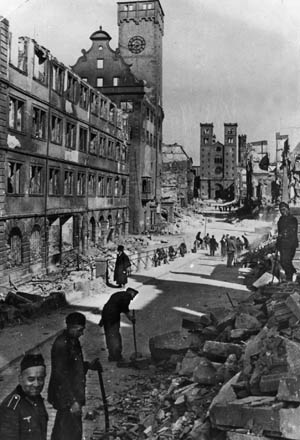 German soldiers and civilians clear rubble from Domstrasse in Würzburg, March 1945. In the distance is St. Kilian's Church, circa 1050.