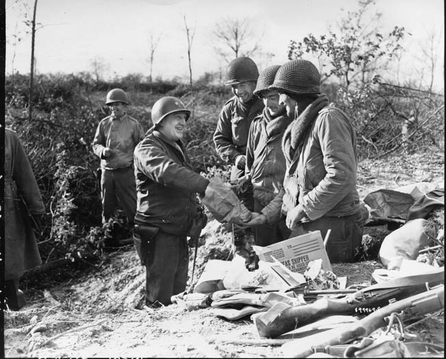 "Major General Norman ""Dutch"" Cota, commander of of 28th Infantry Division, accepts Christmas cookies from one of his men."