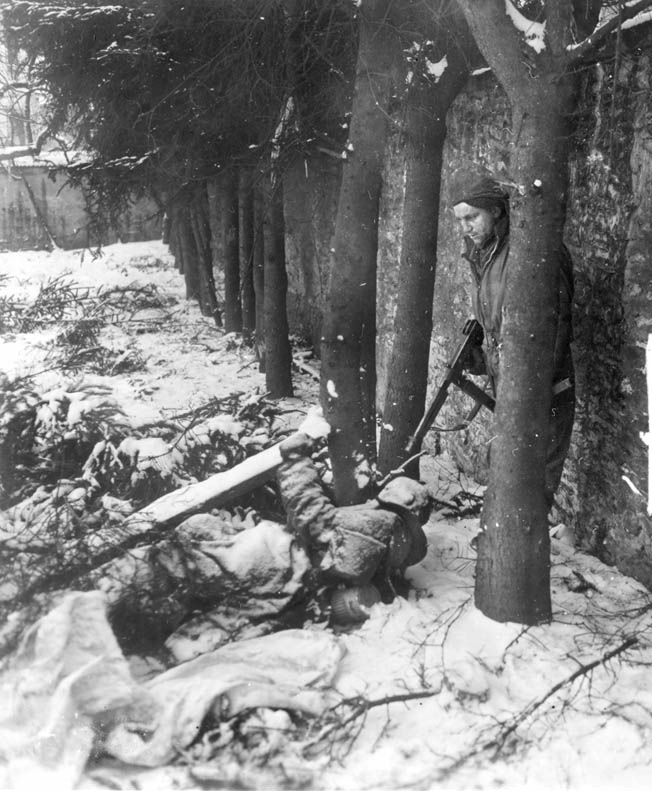 An American soldier with a Thompson submachine gun cautiously inspects a frozen German corpse for possible booby traps near Wiltz, Luxembourg.