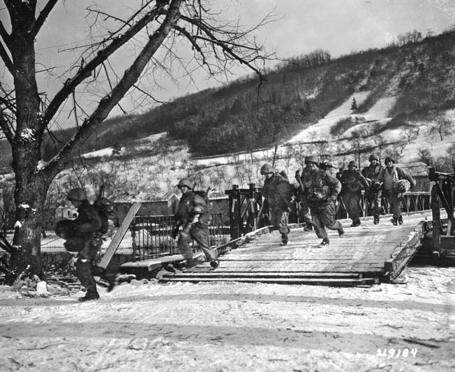 4th Infantry Division troops dash across a Bailey bridge while under enemy fire near Moesdorf, Luxemborg, January 21, 1945.