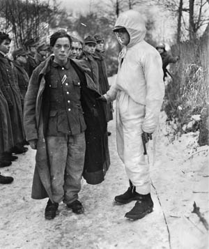 A white-clad soldier from the 8th Regiment, 4th Infantry Division, with young German prisoners captured during fighting in the Sauer River sector.