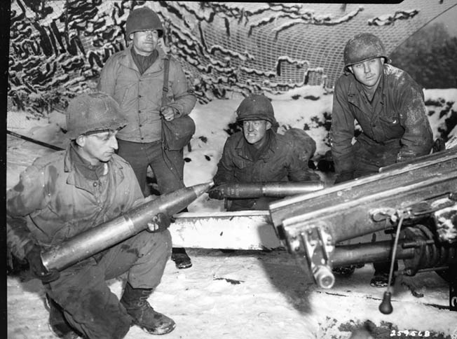 Members of 19th Field Artillery Battalion, 5th Infantry Division, man their gun under a snow-covered cammo net near Haller, Luxembourg.