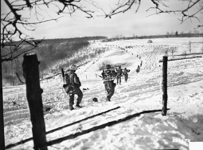 With the German offensive broken, members of the 10th Regiment, 5th Infantry Division pursue the enemy, January 24, 1945.